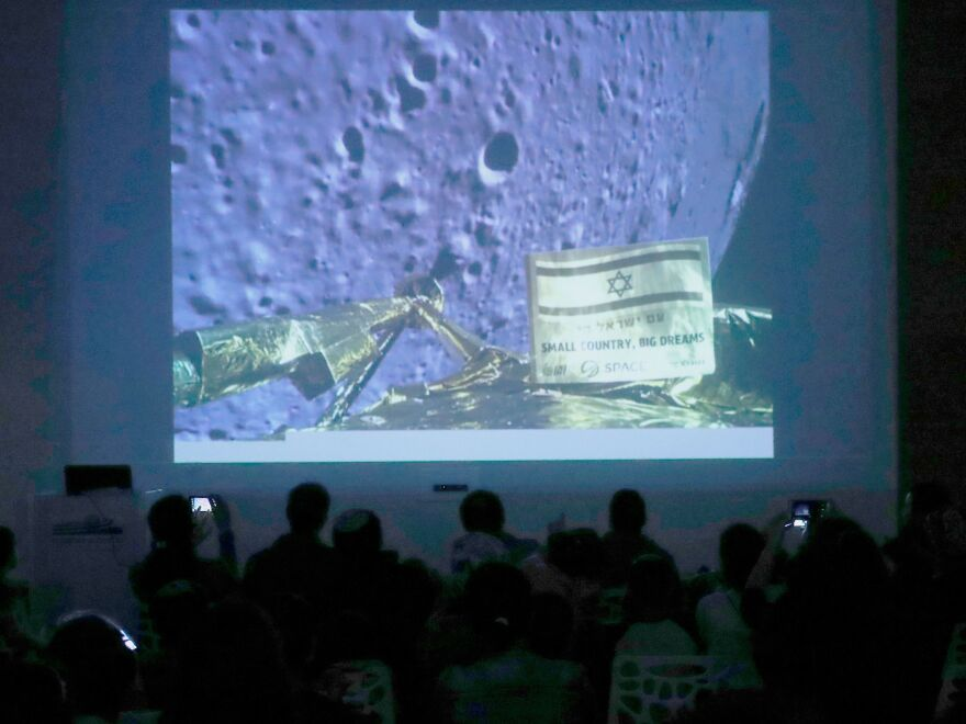 People in the Israeli city of Netanya watching images taken by the camera of the Israel Beresheet spacecraft of the moon surface before it crashed.
