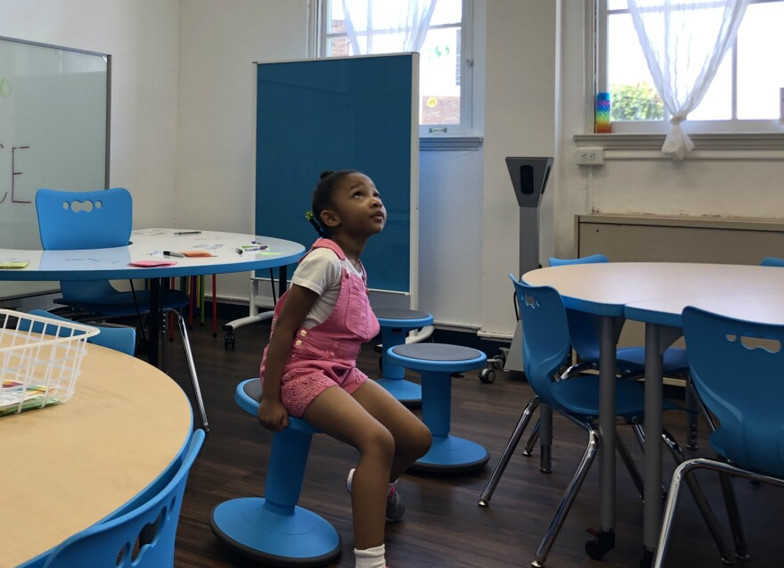 """Arianna Wagner, 5, looks up as an announcement plays on the PA system at a meet-the-teacher event Aug. 9, 2019 at YWLA Primary. She said she likes going to an all-girls school """"because everybody is pretty and I like pretty things."""""""