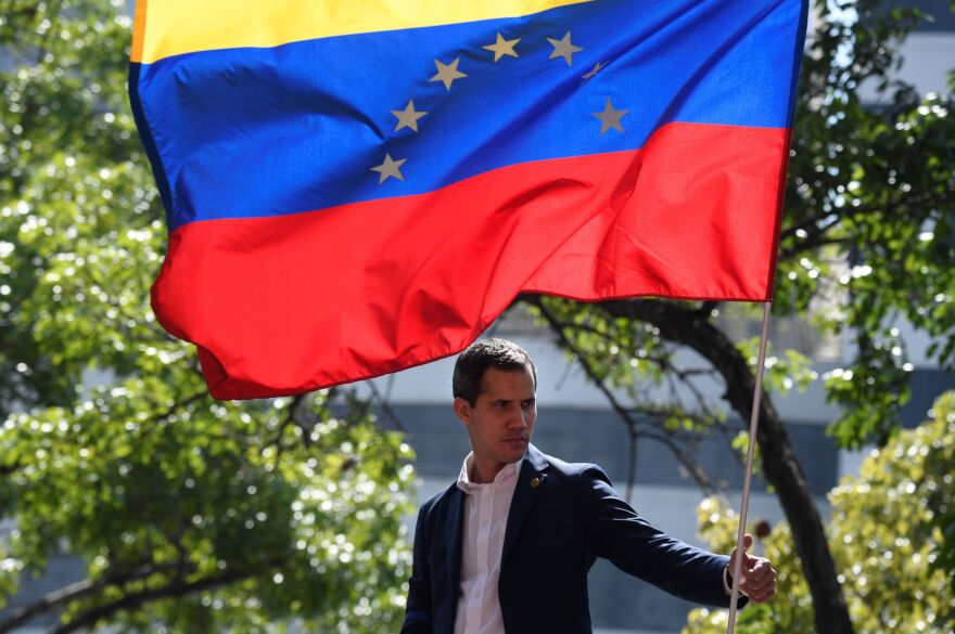 Venezuelan opposition leader and self-proclaimed acting president Juan Guaido stands under the national flag during a gathering with supporters after members of the Bolivarian National Guard joined his campaign to oust President Nicolas Maduro, in Caracas on April 30.