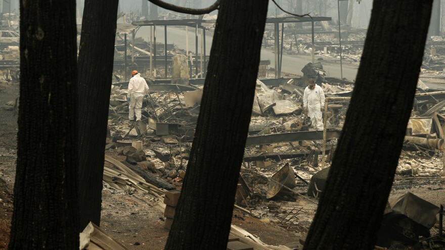Workers search for human remains at a trailer park burned out by the Camp fire, Tuesday, in Paradise, Calif.