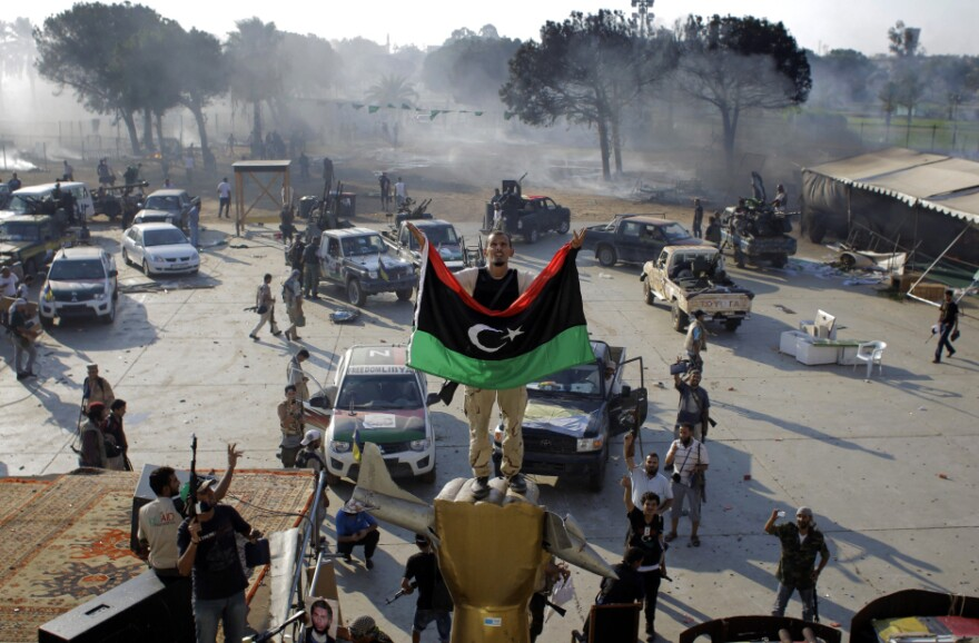 A rebel fighter stands on a monument inside Moammar Gadhafi's main compound in Tripoli.