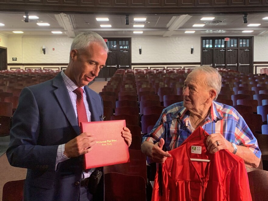 Hillsborough High School Principal Gary Brady presents Joe Perricone with his graduation materials.