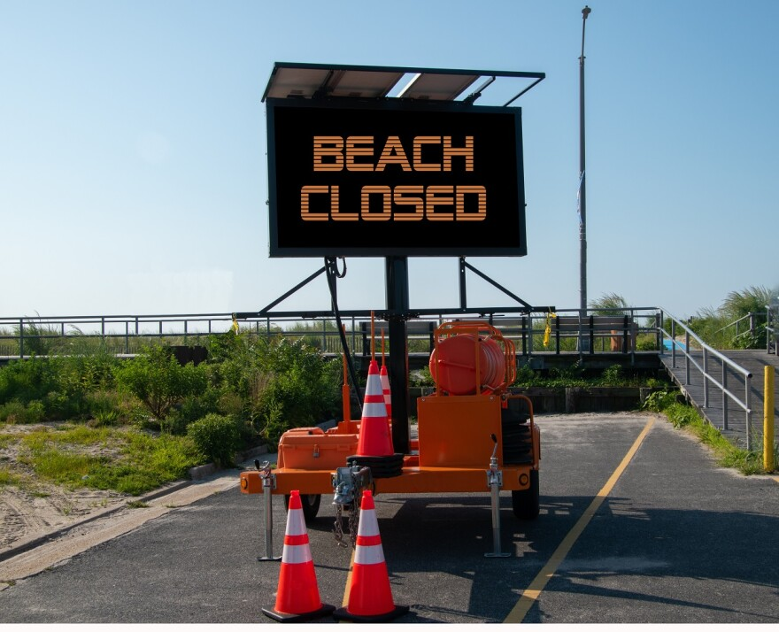 Portable electric digital sign by the a boardwalk ramp at the entrance to a beach that says, Beach Closed