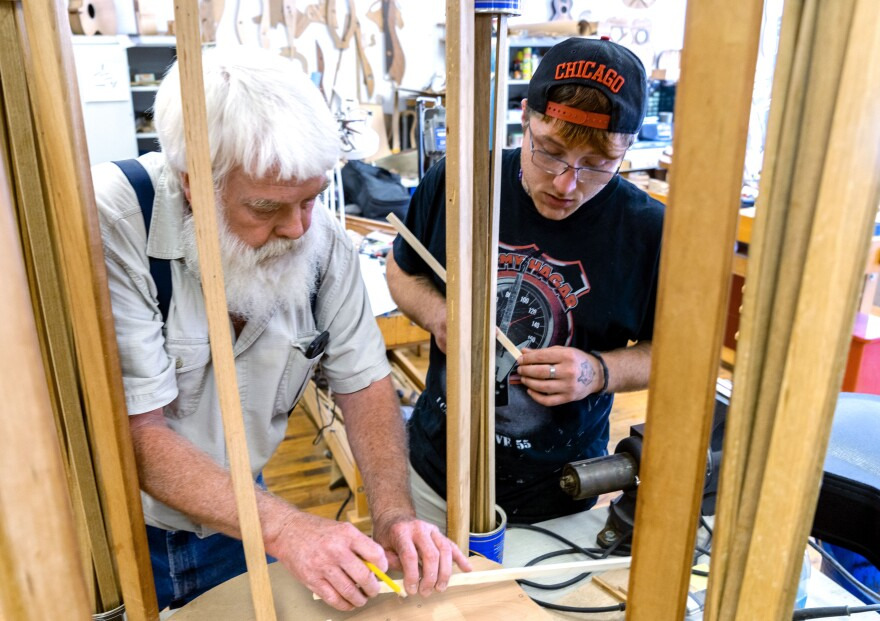 Paul Williams (left) helps Scott build his 'backpack' guitar. It has a smaller body, meant to easily fit in a pack.