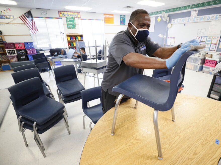 A custodian at a public school classroom in Des Moines cleans a blue chair during the pandemic.