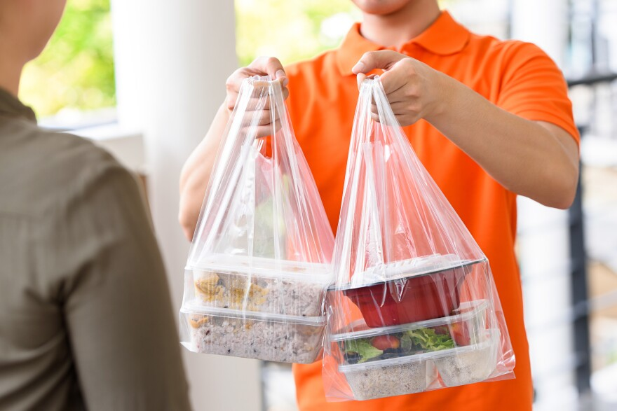 Delivery man in orange uniform delivering food boxes in plastic bags to a woman customer at home.