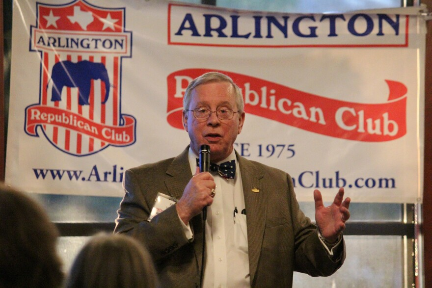 Photograph of Ron Wright dressed in a blazer and bow tie holds a microphone and talks to a crowd at a restaurant in Arlington in 2018. In the background, a white banner with blue and red lettering reads Arlington Republican Club.