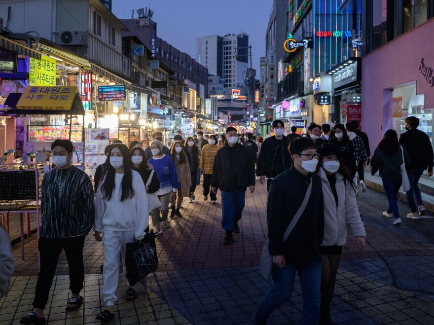 People wearing face masks walk on a street in the Hongdae district of Seoul on Sunday.