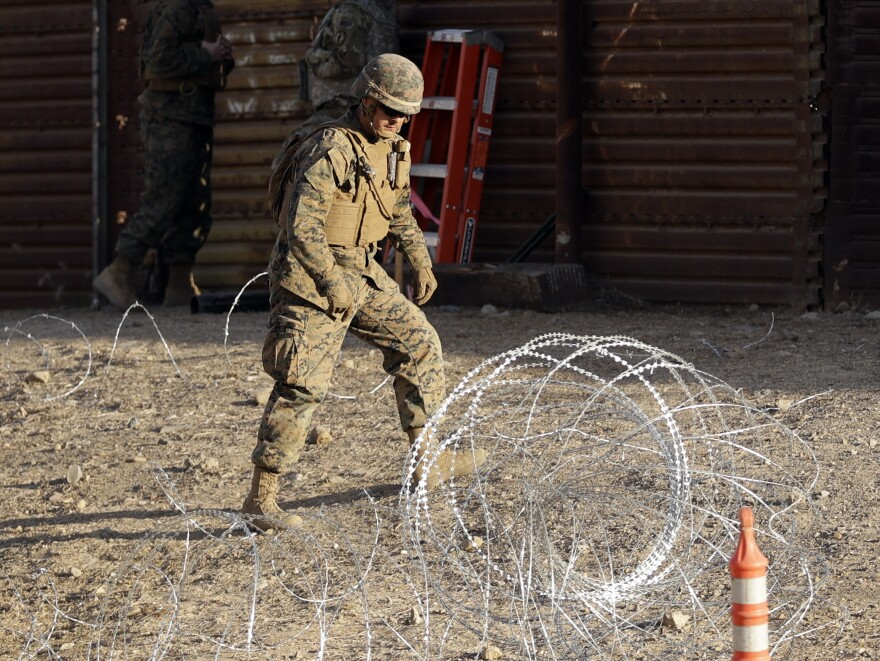 A Marine uses concertina wire to fortify the border separating Tijuana, Mexico, and San Diego, near the San Ysidro Port of Entry.