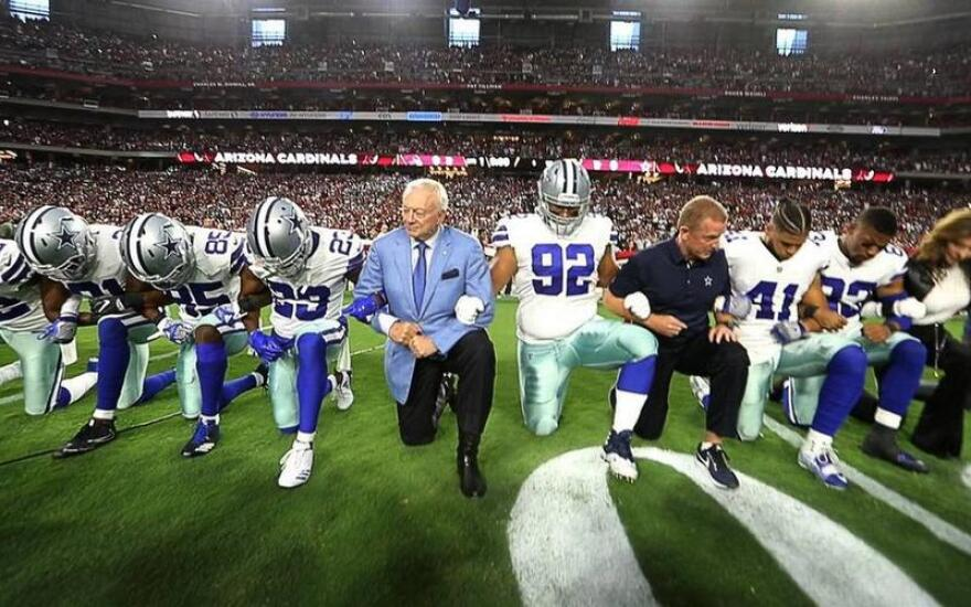 Jerry Jones and the Dallas Cowboys take a knee before a game against the Arizona Cardinals.