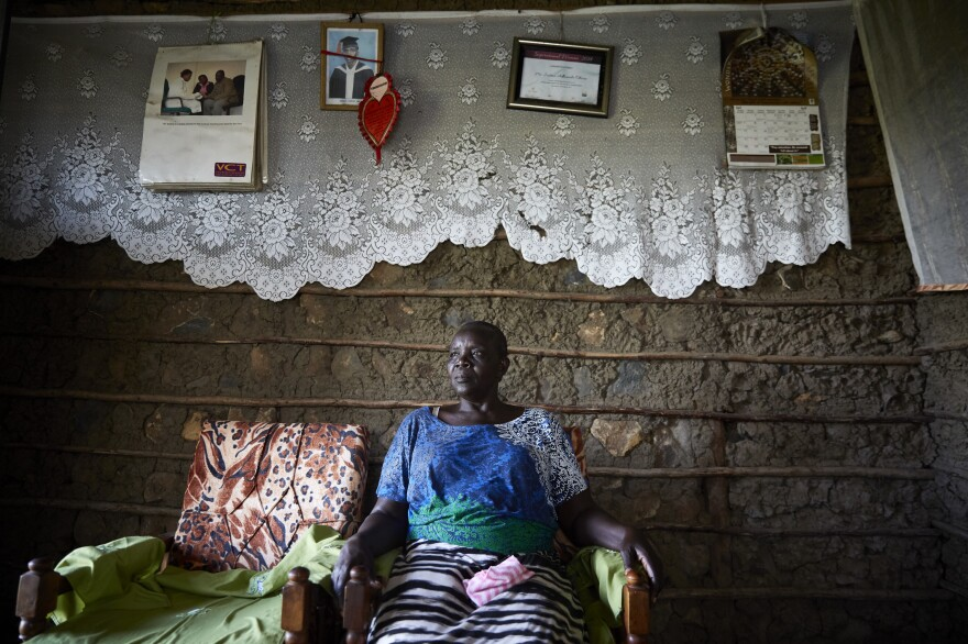 """Justine Adhiambo Obura in her living room at Nduru Beach. A framed certificate naming her """"Inspirational Woman of the Year 2014"""" hangs on the wall."""