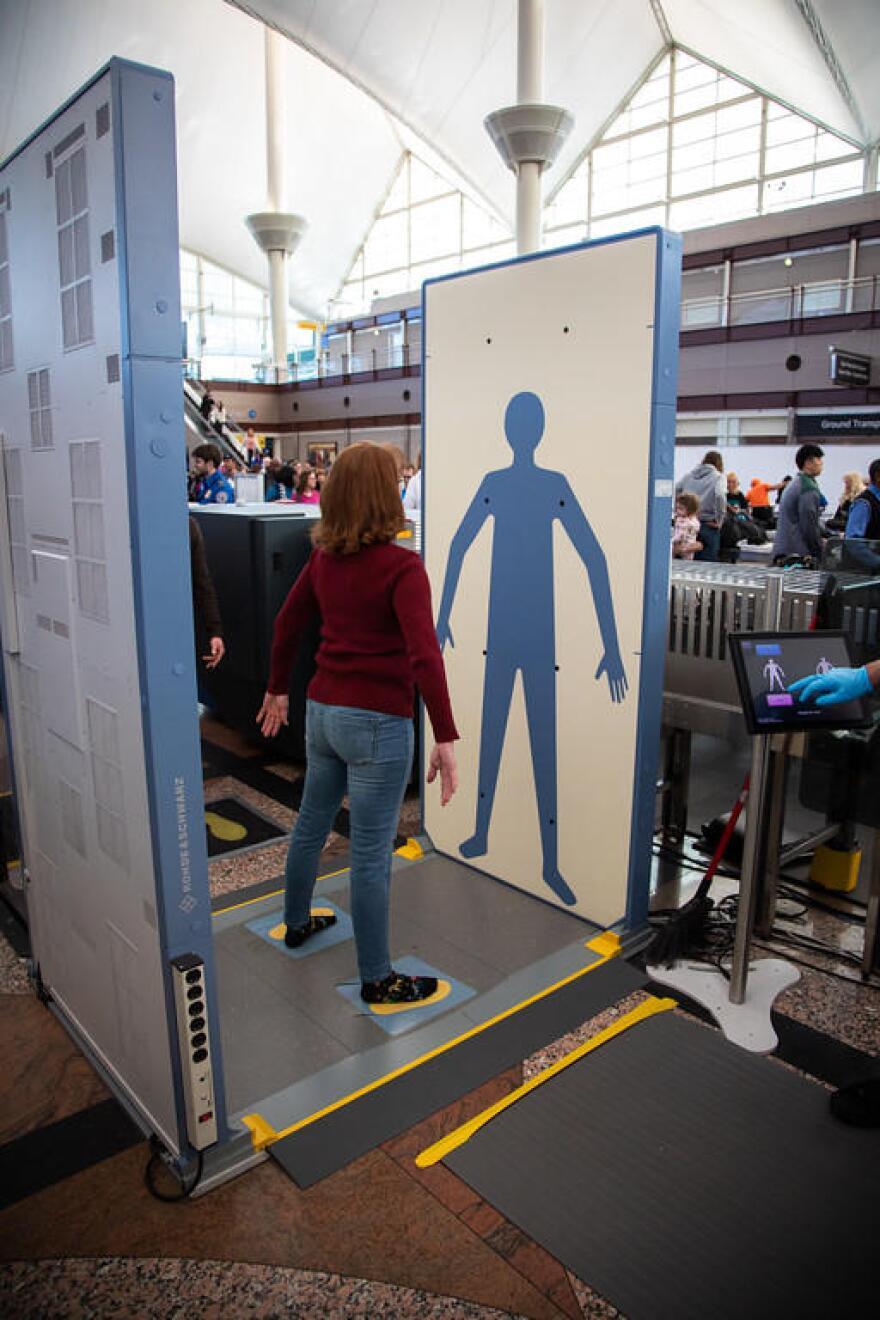 Traveler passing through DIA's new body scanner.