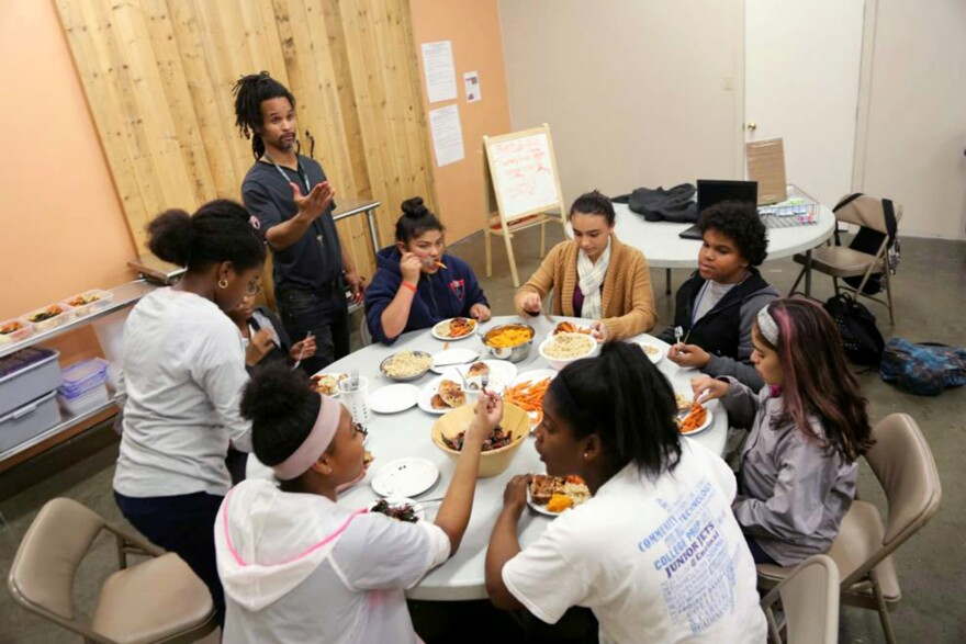Teen volunteers eat together after they finish cooking meals for a local hospital.