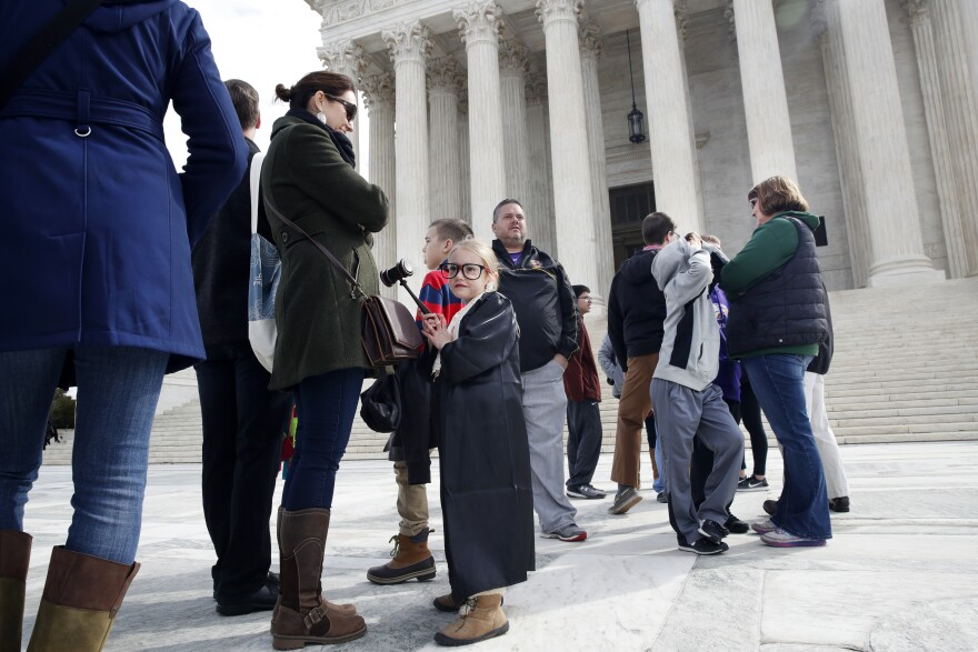 Keegan Herrod (center) dressed as a Supreme Court justice in March. She and her mother Maeve Felle were waiting outside as the court heard arguments in a redistricting case.
