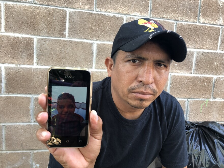 Delmer Lopez holds his cellphone showing a picture of his son. Lopez has lost his asylum case, but decided to send 10-year-old Jose Armando across the bridge alone three weeks ago.