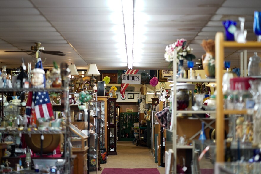 A view of a long hallway full of collectibles and vintage finds stacked on the shelves of an antique store.  Postcards with the Eiffel Tower in Paris are sold at all antique stores in Paris, Texas.