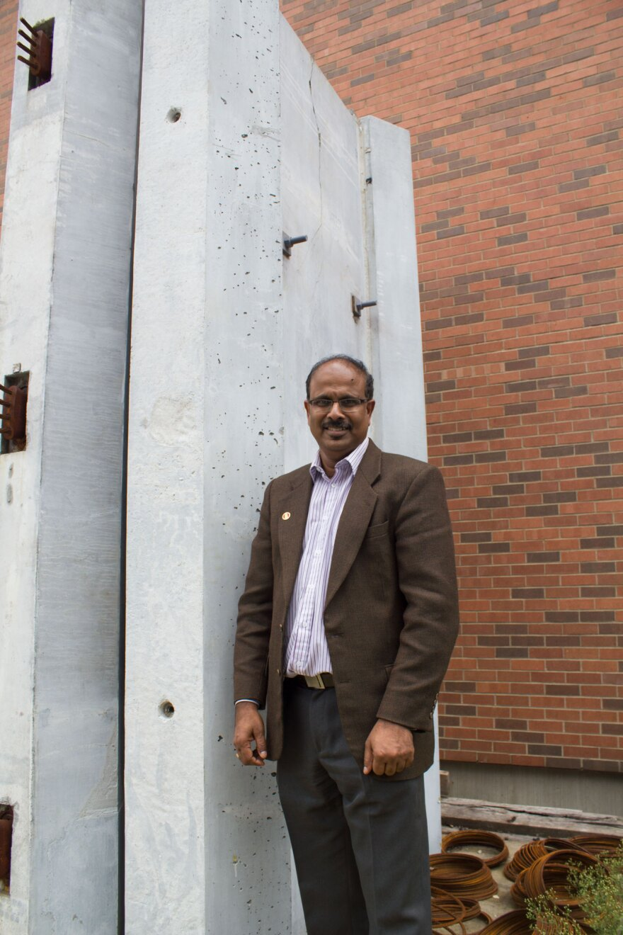 """Sri Sritharan, who's part of Iowa State's Department of Civil, Construction and Environmental Engineering, stands next to a tower made of these """"hexcrete"""" panels and columns. They could allow for turbines that are significantly taller than the current 80-"""