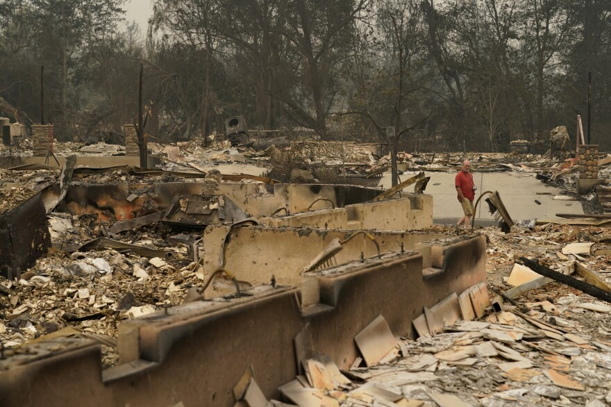A man walks through a neighborhood destroyed by the Almeda Fire on Friday in Talent, Ore.