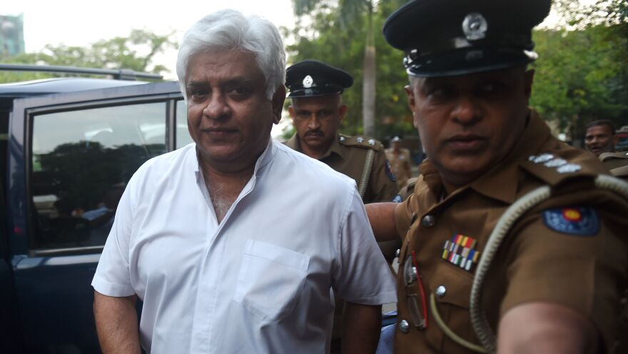 Police arrest Arjuna Ranatunga, Sri Lanka's petroleum minister and former cricket star, in Colombo on Monday. The arrest followed a confrontation in which his bodyguards opened fire on a group of protesters loyal to the president.