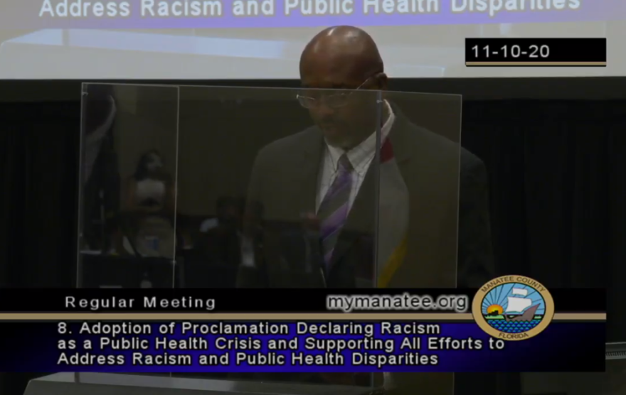 A man in a suit stands behind a podium with a plexiglass safety screen to read a new proclamation.