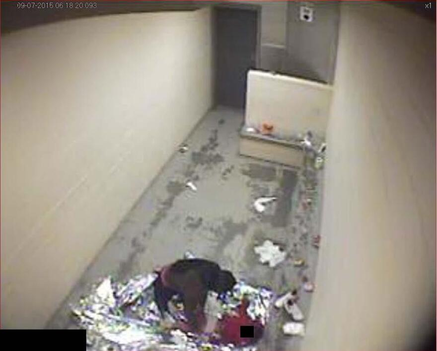 In September 2015, a woman changes a child's diaper on a Mylar sheet in a dirty concrete cell.