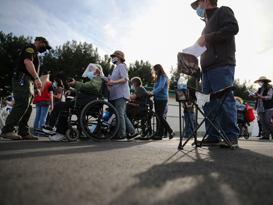 People lined up to receive the COVID-19 vaccine at a mass vaccination site in Disneyland's parking lot in Anaheim, Calif. on Jan. 13. The state says all residents 65 or older are now eligible to receive the vaccine.