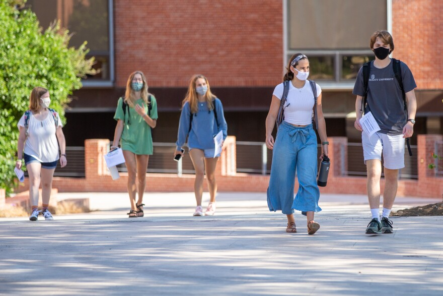 Students in masks walk on the Trinity University campus during the Fall 2020 semester.