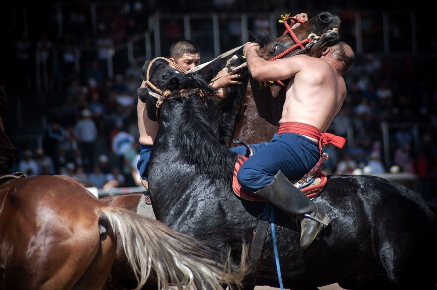 Two competitors engage in er-enish — wrestling on horseback.