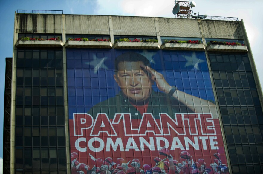"""A huge photograph of Venezuelan President Hugo Chavez is displayed on the facade of state-owned oil company PDVSA (Petroleos de Venezuela) in Caracas on Wednesday. The text reads, """"Move forward, commander."""""""