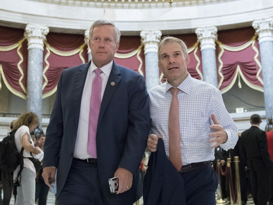 """Rep. Mark Meadows, R-N.C. (left), chairman of the conservative House Freedom Caucus, and Rep. Jim Jordan, R-Ohio, a key member of the group, walk through Statuary Hall at the Capitol last September. Meadows says a vote on immigration will be a """"defining moment"""" with consequences for the Republican Party."""