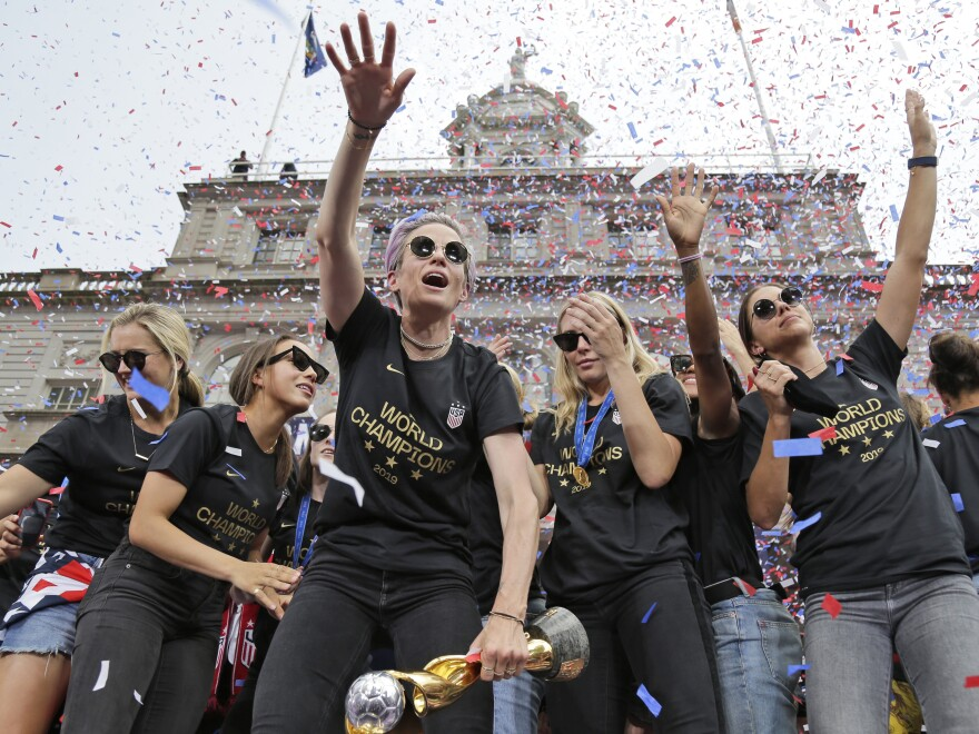"Megan Rapinoe (center) and Alex Morgan (right), pictured celebrating with U.S. women's soccer teammates in New York after a ticker tape parade, on July 10, 2019. ""We are pleased that the USWNT Players have fought for – and achieved – long overdue equal working conditions,"" a spokeswoman for the team said on Tuesday."