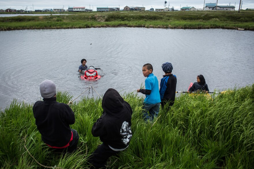 Yup'ik children help recover a snowmobile that sank when its owner attempted to drive across a pond, on June 30, 2015, in Newtok.