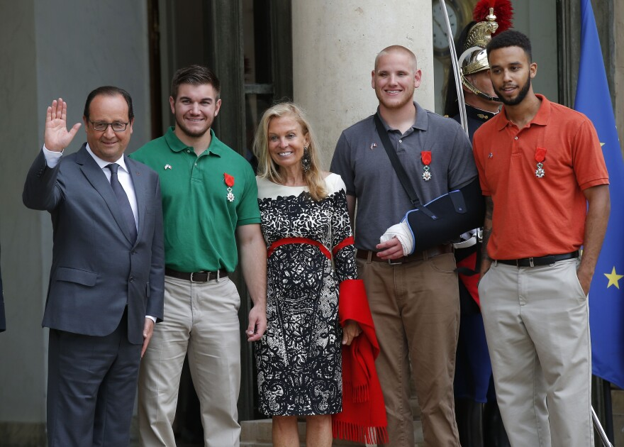 French President Francois Hollande and U.S. Ambassador to France Jane D. Hartley stand with (from left) Alek Skarlatos, Spencer Stone and Anthony Sadler as they leave the Elysee Palace in Paris. The three American men, along with a British citizen, were pinned with Legion of Honor medals Monday morning for tackling a gunman on a train.