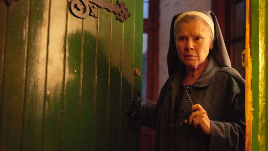 A mischievous nun (Imelda Staunton) welcomes a stranger into a decrepit house in the supernatural thriller <em>Amulet</em>.
