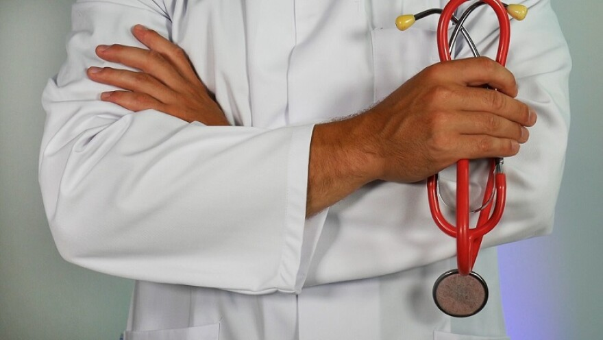 Person wearing white doctor's coat stands with arms crossed holding a stethoscope.
