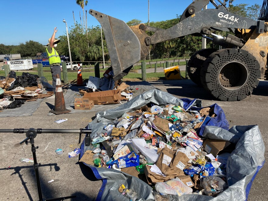 pile of garbage and recycled items, with man and front-end loader behind it