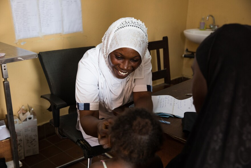 Nabia Drammeh, 27, a nurse, talks with Maram Ceesay, and her granddaughter, Awa at the Brufut Minor Health Center outside of Banjul, the capital of the Gambia. Awa's mother passed away during childbirth leaving Maram to look after her. The 2-year-old is being treated for pneumonia.