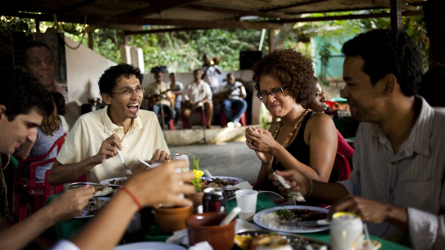 Residents enjoy a meal at the Quilombo Sacopa in Rio de Janeiro in 2012. Brazil has some 3,000 <em>quilombo</em> communities, which were formed by runaway slaves, dating to the 19th century. Residents have been promised ownership of their land but say the legal process has moved slowly.