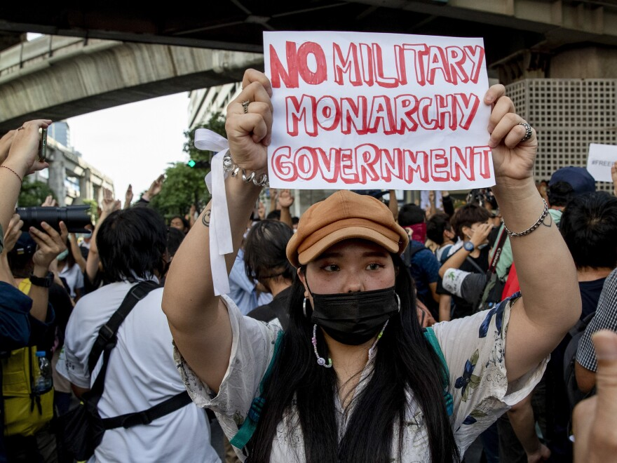 A pro-democracy protester shows a sign during a protest at a main road in the Central business district in Bangkok, Thailand, on Thursday.