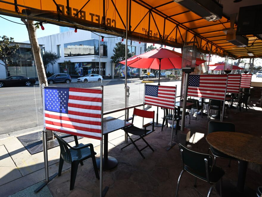 Empty patio tables are seen at a diner in West Hollywood, Calif. on Nov. 30, 2020, after Los Angeles County banned outdoor dining amid the pandemic. The struggles being experienced by restaurants and retailers are expected to have led to sharply slower job growth last month.