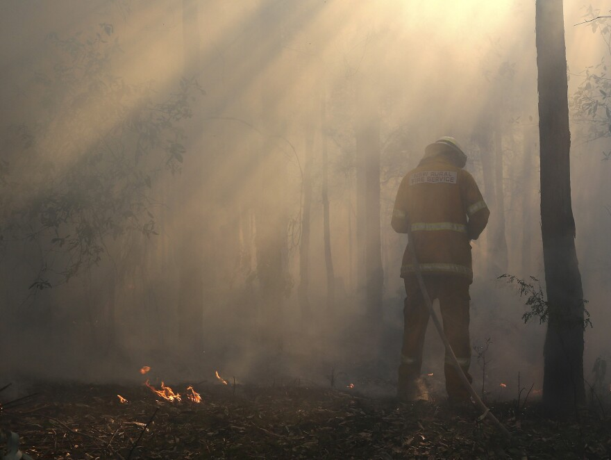 Flames flicker near Bilpin, Australia, as a firefighter finishes securing the area on Wednesday.