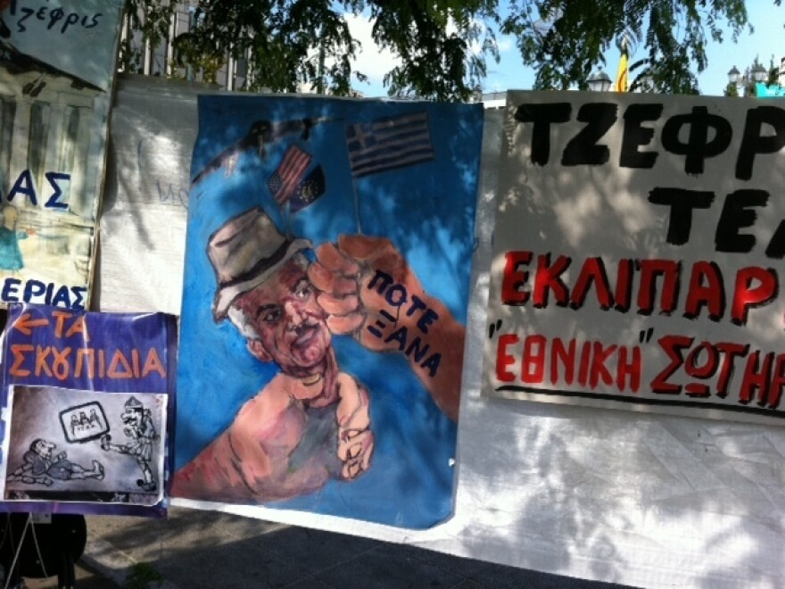 "<p>A poster depicts Greek Prime Minister George Papandreou as an American puppet. The words on the hand hitting Papandreou's face are ""never again"".</p>"