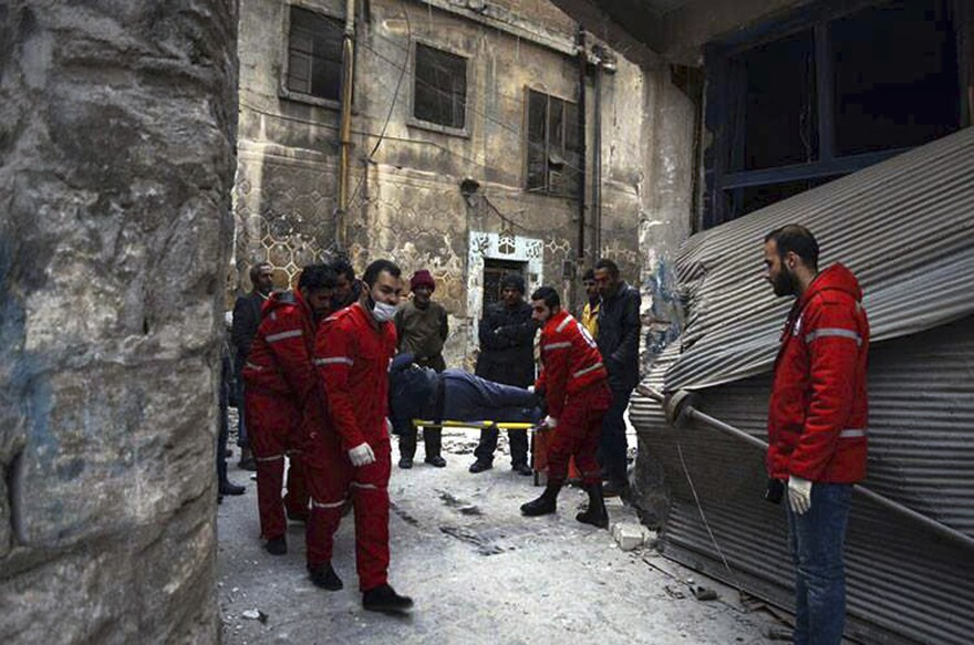 Members of the Syrian Arab Red Crescent carry a patient on a stretcher out of a medical facility in the Old City of Aleppo, Syria, on Wednesday.