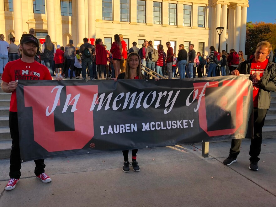 Photo of U of U students holding a sign that says In Memory Of Lauren McCluskey.