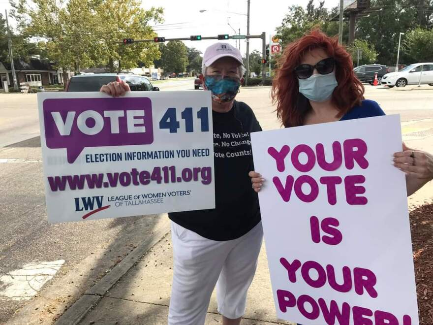 Two masked women holding signs on a street corner