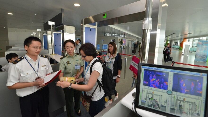 Chinese customs officials, like the ones shown here in August at the Lukou International Airport in Nanjing, have broad powers to confiscate items. One woman who had copies of her father's memoir seized has sued the government.