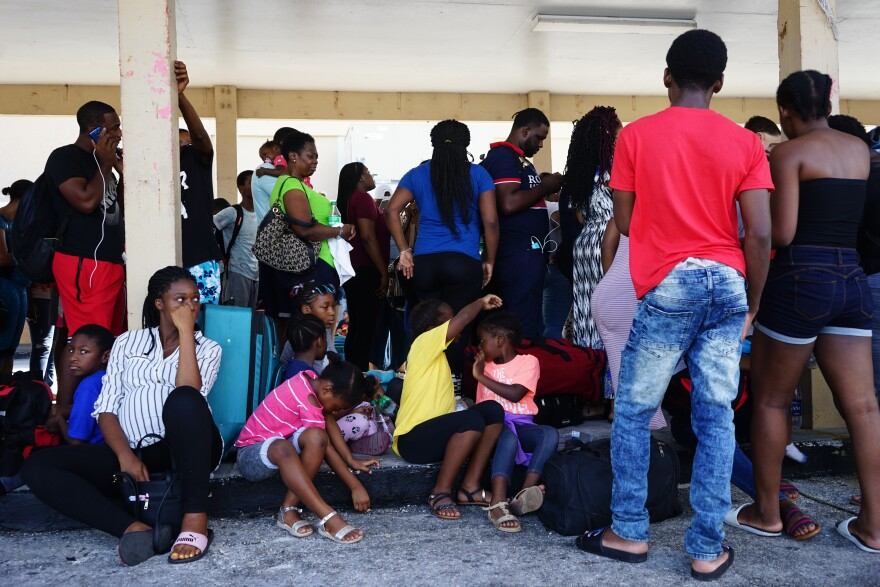 A crowd of people gathered at Freeport Harbour in Grand Bahama trying to board a cruise ship to Florida.