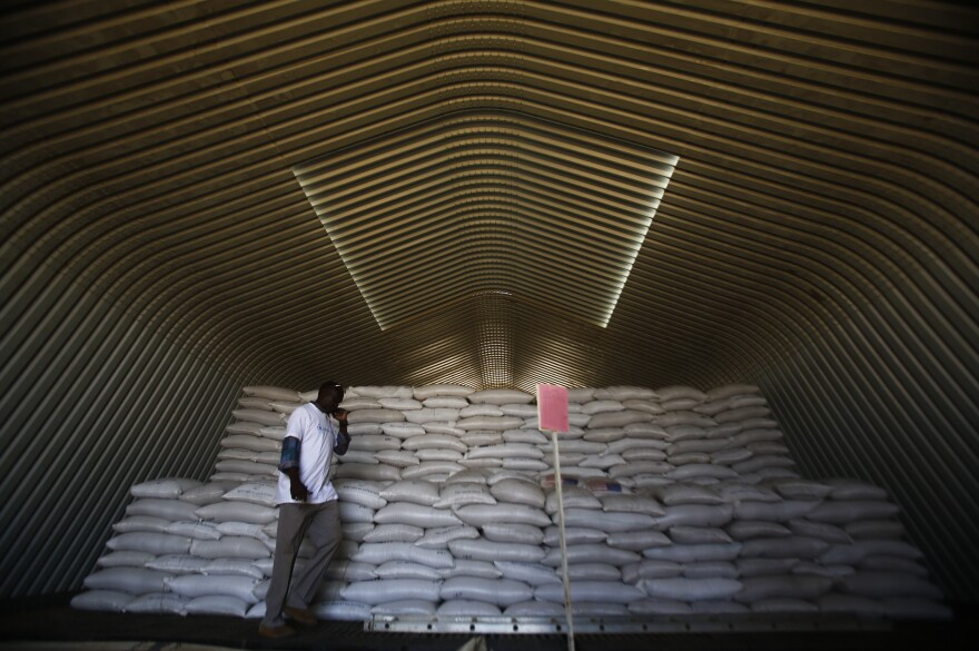 A World Food Programme worker stands next to aid parcels that will be distributed to South Sudanese refugees at the airport in Sudan's North Kordofan state.