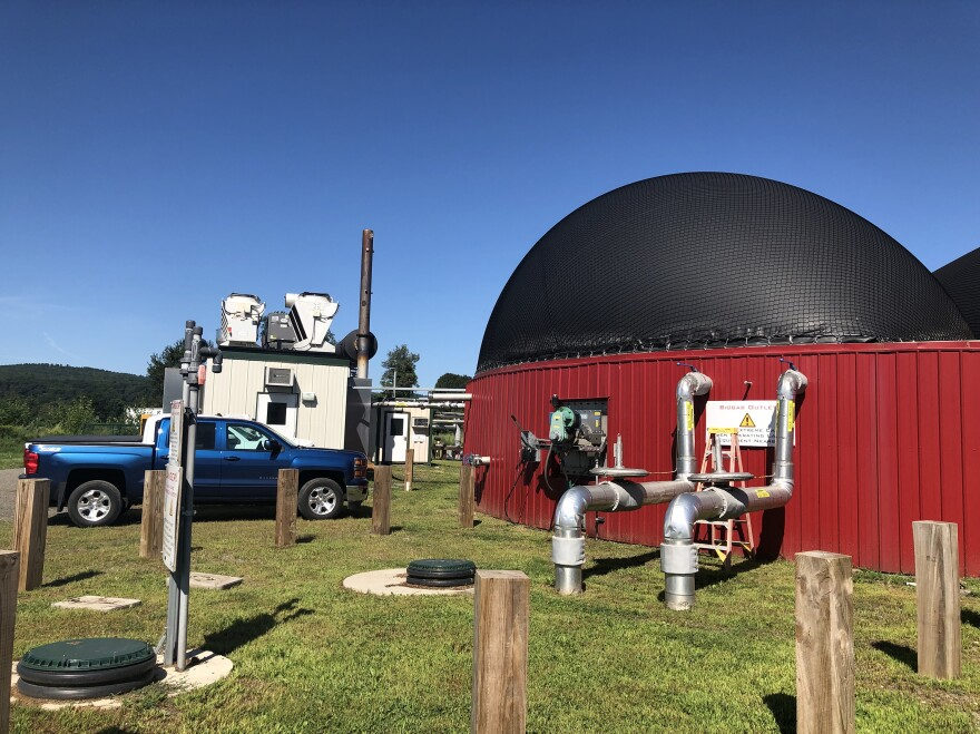 In the digester on his farm, Melnik combines food waste from Whole Foods and other local sources with manure from his cows. The mixture cooks at about 105 degrees Fahrenheit. As the methane is released, it rises to the top of a large red tank with a black bubble-shaped dome.