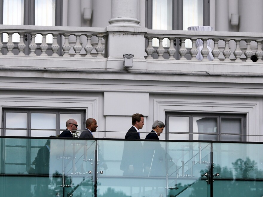 Secretary of State John Kerry (right) walks using crutches Thursday at the garden of the hotel where the Iran nuclear talks are being held in Vienna.